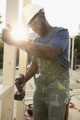 Man using power drill, working at construction site - HEROF07077