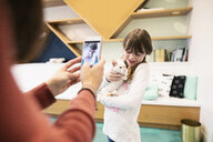 Mother with camera phone photographing daughter holding kittens in cat cafe - HEROF07146