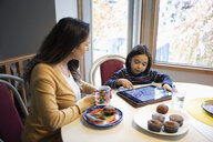 Mother watching son using digital tablet at kitchen table - HEROF07167
