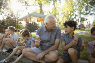 Grandfather and grandson eating ice cream cones on curb at summer neighborhood block party in park - HEROF07203