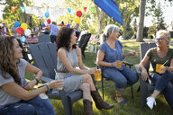 Female neighbors talking and drinking at summer neighborhood block party in park - HEROF07209