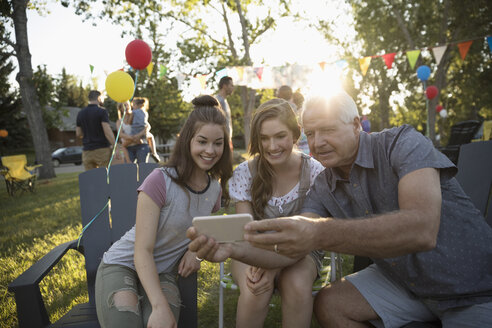 Grandfather and granddaughters taking selfie with camera phone at summer neighborhood block party in park - HEROF07212