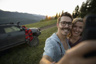 Happy couple taking selfie with camera phone in front of SUV on mountain road - HEROF07227