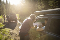 Friends with map on overland adventure in SUVs on sunny remote forest road - HEROF07230
