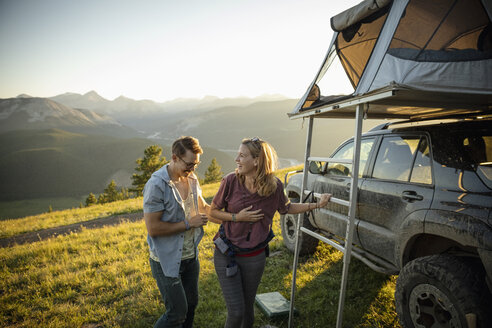 Happy couple climbing into SUV rooftop tent in idyllic mountain field, Alberta, Canada - HEROF07233