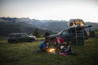 Friends camping, enjoying campfire on remote mountain hilltop, Alberta, Canada - HEROF07239
