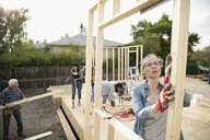 Female volunteer lifting frame, helping build house - HEROF07257