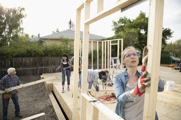 Female volunteer lifting frame, helping build house - HEROF07257