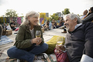 Happy senior couple relaxing, drinking wine and waiting for movie in park to start - HEROF07263