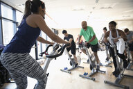 Female instructor on exercise bike leading spin class in gym - HEROF07359