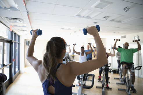 Female instructor with dumbbells leading spin class in gym - HEROF07368
