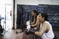 Female boxer with tattoos resting in gym - HEROF07386