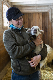 Female farmer holding baby lamb in barn - HEROF07392
