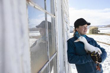 Female farmer holding duck outside barn - HEROF07395