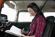 Female pilot filling out log book in airplane cockpit - HEROF07401