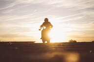 Silhouette of man riding custum motorcycle at sunset - OCMF00224