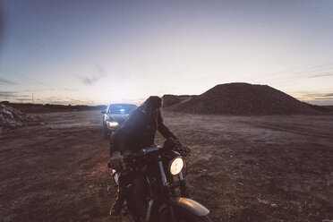 Spain, Madrid, Man with motorcycle and dreadlocks mocks policeman - OCMF00227