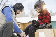 Father tying ice-skates for son - HEROF07454