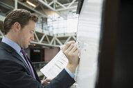 Businessman writing on whiteboard in office - HEROF07475