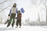 Father and son holding snow shovels on ice rink - HEROF07493
