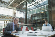 Businessmen using laptops at conference table - HEROF07568