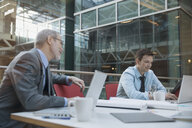 Businessmen using laptops at conference table - HEROF07571