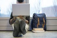 College student using laptop on floor - HEROF07574