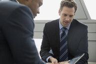 Businessmen using digital tablet in meeting - HEROF07595