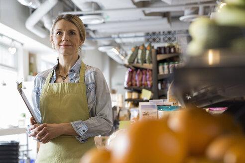 Confident worker with clipboard in market - HEROF07607