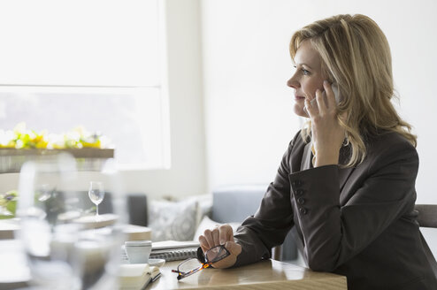 Businesswoman talking on cell phone at bistro table - HEROF07634