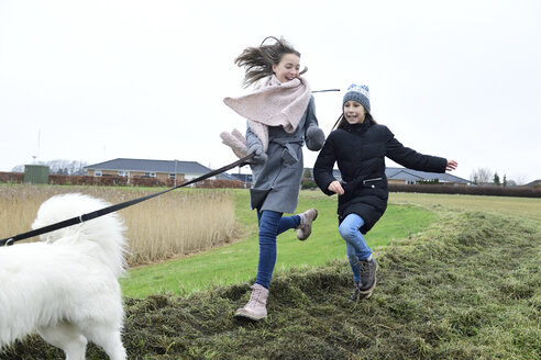 Two girls running on a meadow with dog having fun - ECPF00257