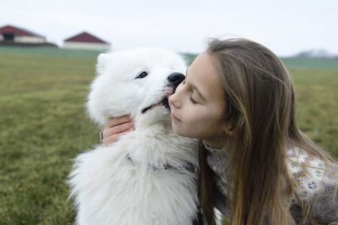 Girl and her white dog cuddling on a meadow - ECPF00260