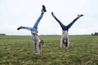 Two girls doing handstand on a meadow - ECPF00263