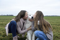 Two girls crouching on a meadow kissing dog - ECPF00266