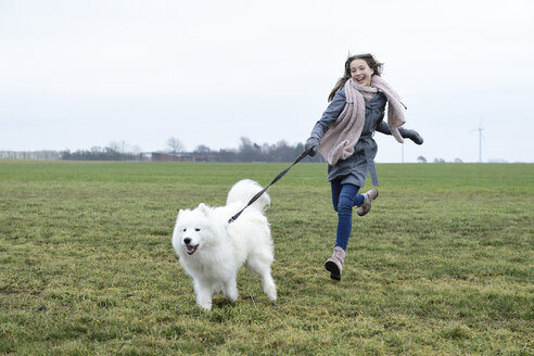 Laughing girl running on a meadow with her dog - ECPF00269