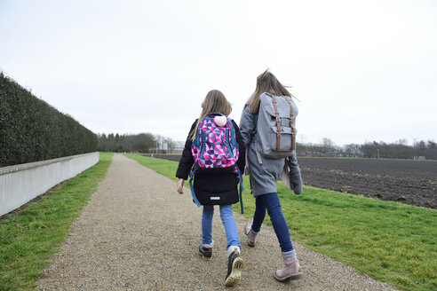 Two sisters with backpacks walking side by side - ECPF00272