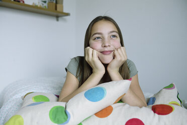 Portrait of smiling girl lying on bed - ECPF00275