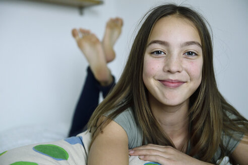 Portrait of smiling girl lying on bed - ECPF00278