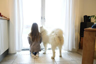 Back view of girl and her dog looking through French door - ECPF00281