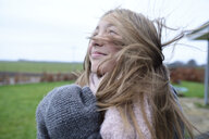 Portrait of smiling girl with blowing hair in winter looking up - ECPF00293