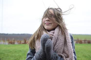 Portrait of smiling girl with blowing hair in winter looking up - ECPF00296