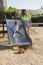 Mother with daughter on slide on a playground - MAUF02404