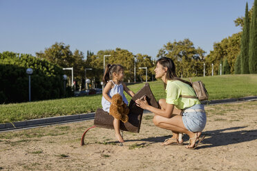 Happy mother with daughter on a playground - MAUF02407