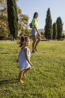 Little girl walking on lawn in a park with her mother - MAUF02416