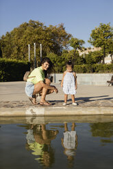 Happy mother with daughter looking at their mirror image in a pool in a park - MAUF02422
