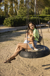 Smiling mother with daughter sitting on tire swing on a playground - MAUF02428