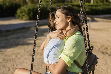 Smiling mother hugging daughter on a playground - MAUF02431
