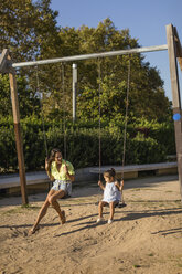 Happy mother and daughter on a swing on a playground - MAUF02434
