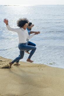 Spain, Barcelona, happy couple having fun on the beach - BOYF01273