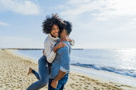 Spain, Barcelona, happy couple hugging on the beach - BOYF01279